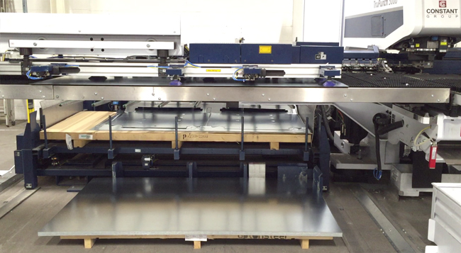 New piece of sheet metal is positioned automatically and aligned onto the bed of the punching machine.